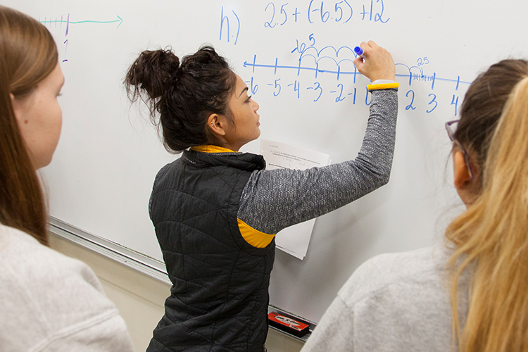 A student writes a math problem on a white board.