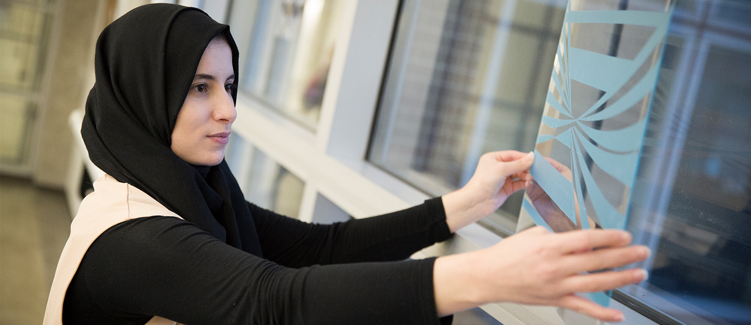 Asal Issa places her design in a window at the School of Architecture and Urban Studies.