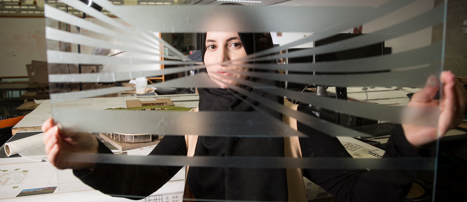 An architecture student looks through a window she designed.