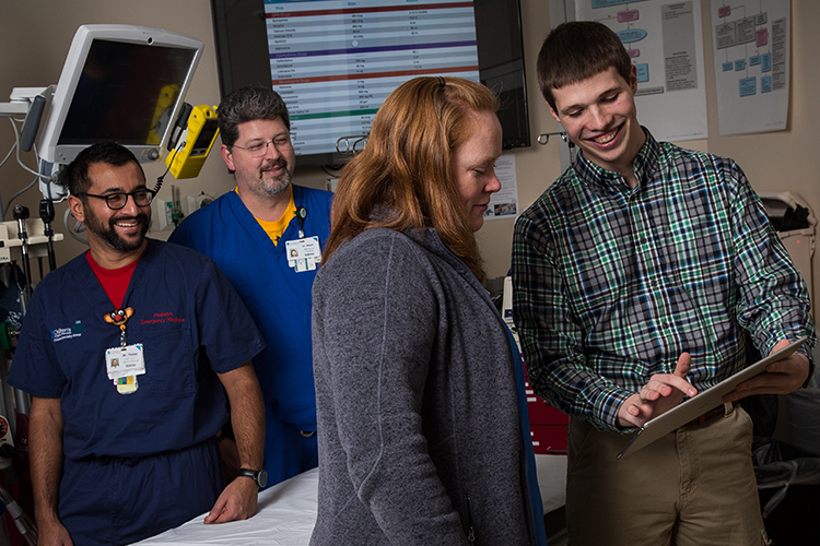 UWM student Evan Timmermann demonstrates a pediatric emergency app for doctors at Children's Hospital of Wisconsin. (UWM Photo/Troye Fox)