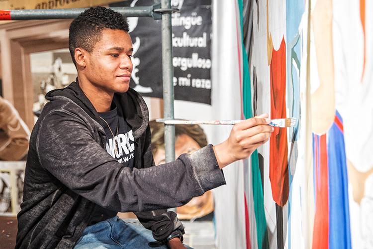 A student paints a mural.