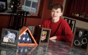 Brennon Colburn poses with a flag, photo and other items that remind him of his father.