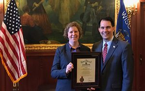 Rebecca Neumann, associate professor of economics at UWM, receives a 2016 Governor's Financial Literacy Award from Gov. Scott Walker at the Wisconsin Capitol. (Submitted photo)