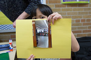 A student from Burma shows off the book she is making about her school.