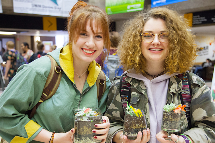 Two UWM students smile as they hold the terrariums they made out of recycled glass jars.
