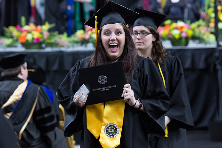 Graduate holds up her diploma.