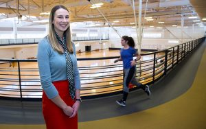 Stacy Gnacinski stands in the Klotsche Center as a jogger goes past.