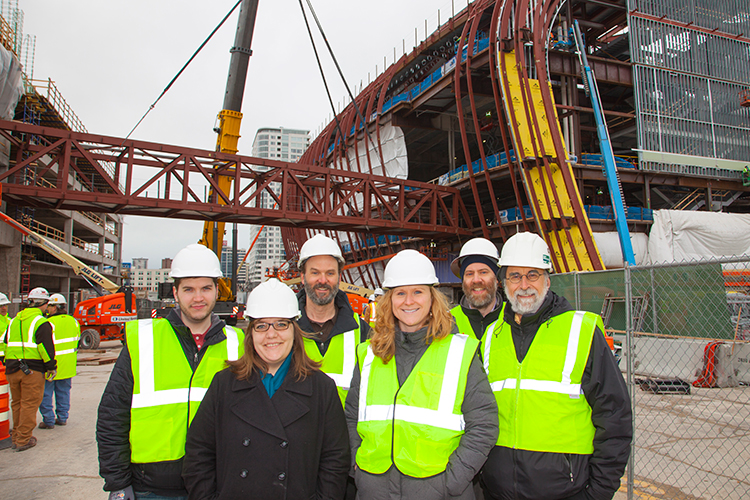 UWM alums stands in from of a skywalk for the new Bucks arena.