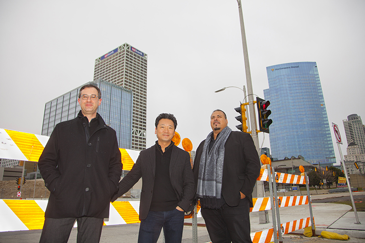 Architects stand on a downtown street.