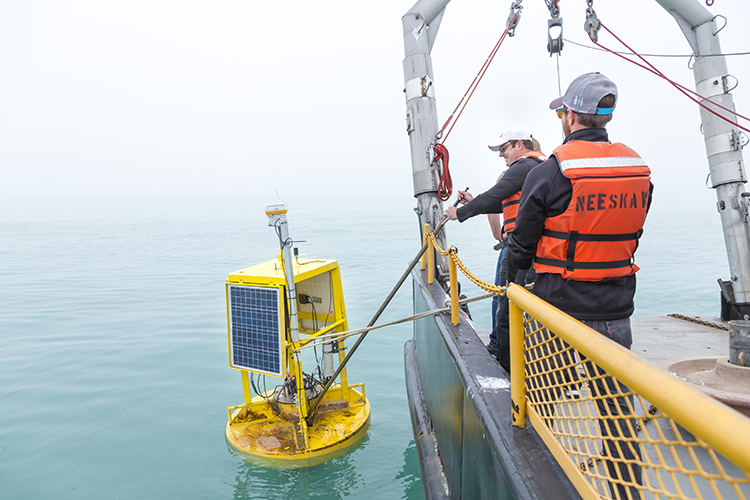 The buoy arrives at it's designated coordinates, is placed in the water, and Todd Miller does the final push off.