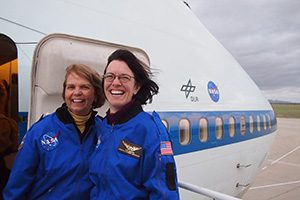 Two women stand outside a large airplane.