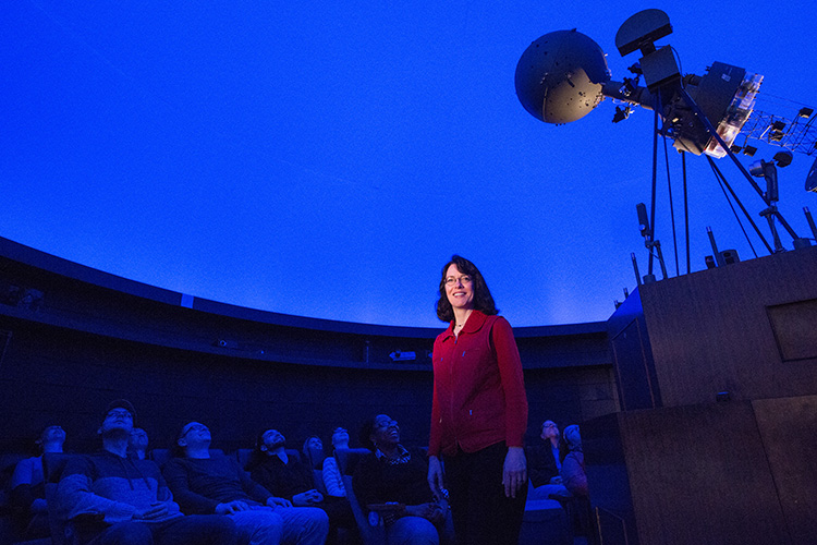 Jean Creighton stands in the planetarium with a blue background.