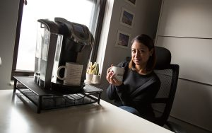 Ira Driscoll sits at her desk drinking coffee.