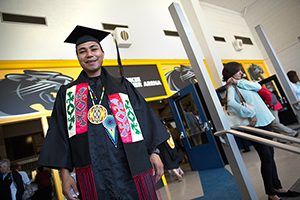 James Flores poses in his graduation robe