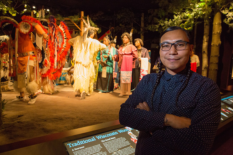 James Flores stands in front of a diorama depicting American Indian life.