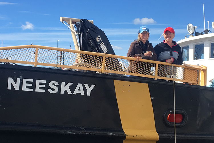 Two women stand at the railing of the research ship Neeskay.