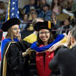 Adviser places the hood on graduate