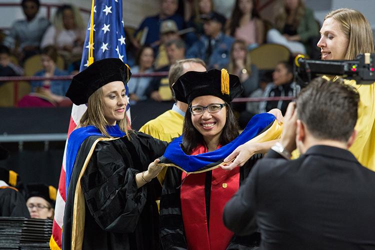 Adviser places the hood on graduate
