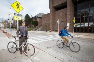 Professor stands next to his bike while another bicyclist whizzes past.