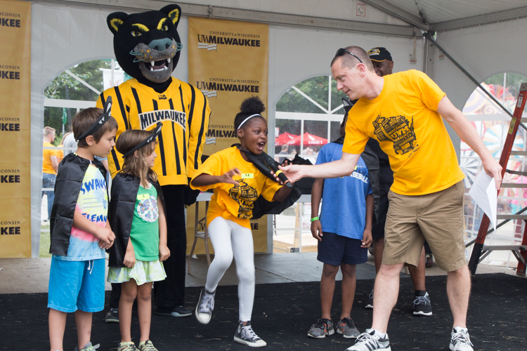 Children roar into a microphone with UWM mascot Pounce standing nearby