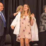 A nursing student puts on a white coat with help from another woman.