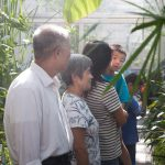 A family consisting of two grandparents, a mother and two sons explores the UWM greenhouse.
