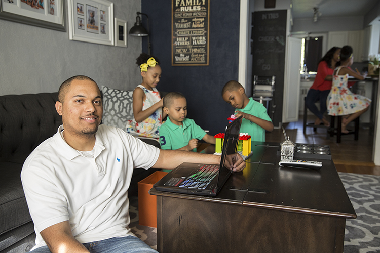 Jordan Acevedo sits on the floor with his laptop while his children play nearby and his wife works with their daughter in the background.
