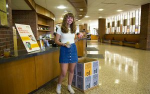 Alyssa Molinski is standing by food donation box in the Golda Meir Library.