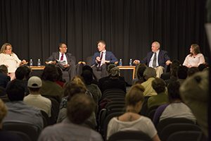 Panelists sit on a stage in front of a large crowd.