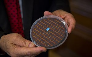 A man holds a disk containing numerous small sensors.