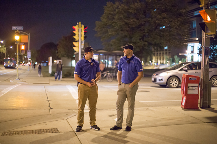 Two students stand on a street corner at night.