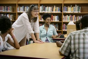 UWM Professor Vickie Moerchen leans on a table and smiles while talking to students.