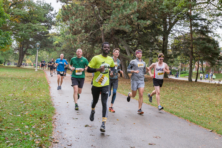 Racers run on a concrete path through Lake Park.