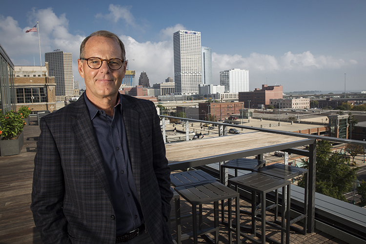 Eppstein Uhen Architect Greg Uhen smiles for a portrait with downtown Milwaukee as the backdrop