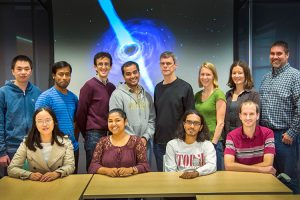 Physicists pose for a photo in front of a space image.