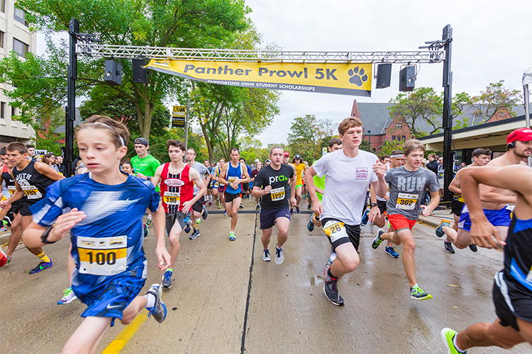 "Runners race away from the starting line under a sign that reads ""Panther Prowl 5K"""