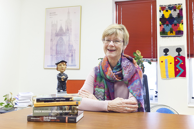 Merry Wiesner-Hanks sits at her desk with a Martin Luther bobblehead.