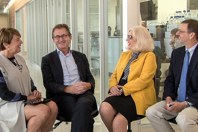 Four panel members smile
