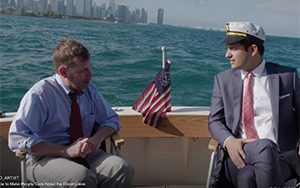 Egan and Kosta ride in a boat with the Chicago skyline in the background.