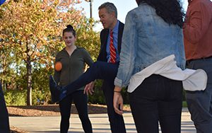 Mark Mone kicks a hacky sack while students watch.