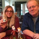 Glocka and Klette sit at a table with figurines of characters.