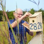 Pete Dunn looks into a birdhouse on a pole in a field.