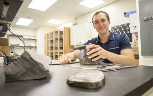 Erik Gulbranson sits at a table in a lab with samples of rock.