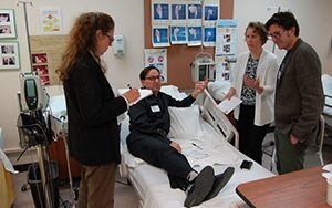 Three people gather around a hospital bed containing someone acting as a patient.