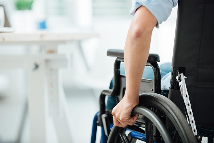 Hand on wheelchair wheel