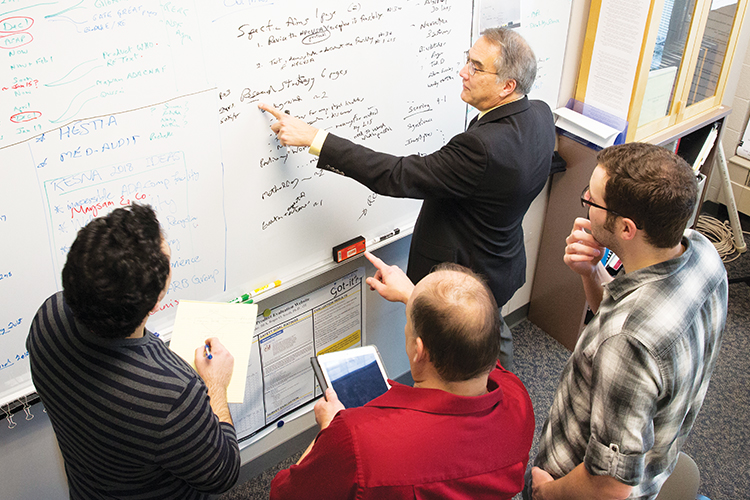 Roger O. Smith works on a problem with members of his research team