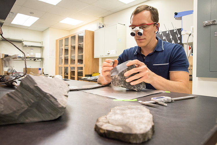 Paleoecologist Erik Gulbranson studies some of the fossilized trees he brought back from Antarctica.