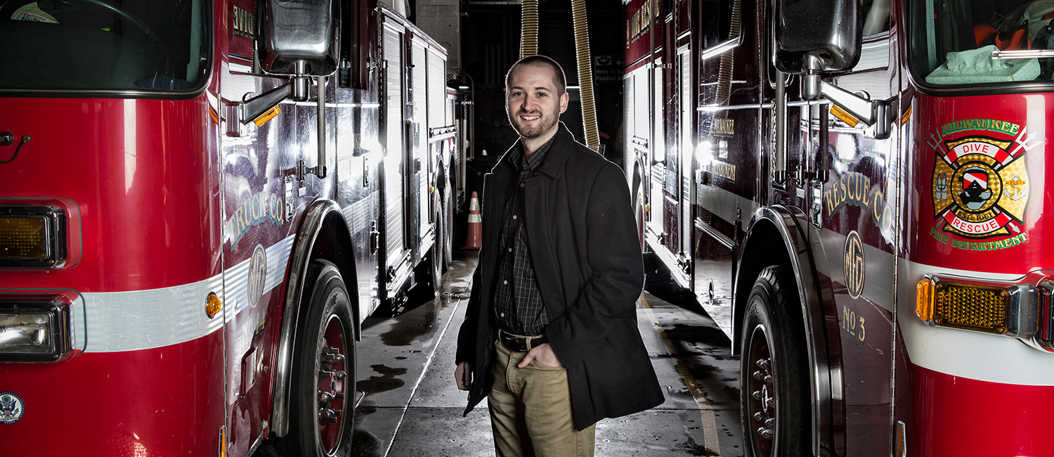 Graduate student David Cornell standing between two fire trucks