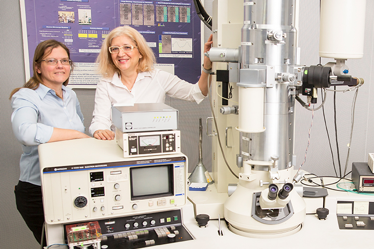 Professors Carol Hirschmugl and Marija Gajdardziska stand in a lab.