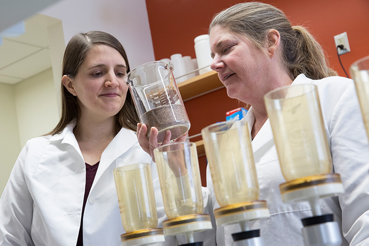 Two researchers look at a vial of sand.